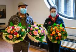 Guido Rigon und Kim Schwarzkopf mit Mundschutz und Blumensträußen