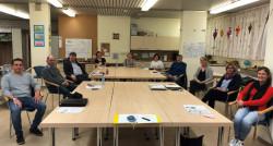 Mitglieder einer Arbeitsgruppe des Integrationsausschusses sitzen an Tischen