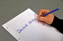 Deutsch-Kurs steht auf einem Papier. Eine Hand hält einen Stift.