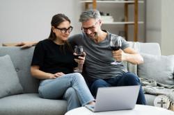 Pärchen mit Wein vor Laptop