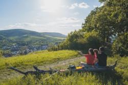Eine Familie sitzt auf einem Baumstamm und genießt die Aussicht in Tal