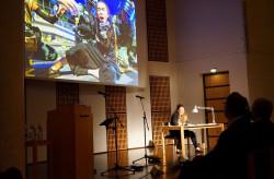 Barbara Stoll liest bei der Verleihung des Hansel-Mieth-Preises Teile der Gewinner-Reportage vor, während im Hintergrund die eindrücklichen Fotos dazu an die Wand projiziert werden